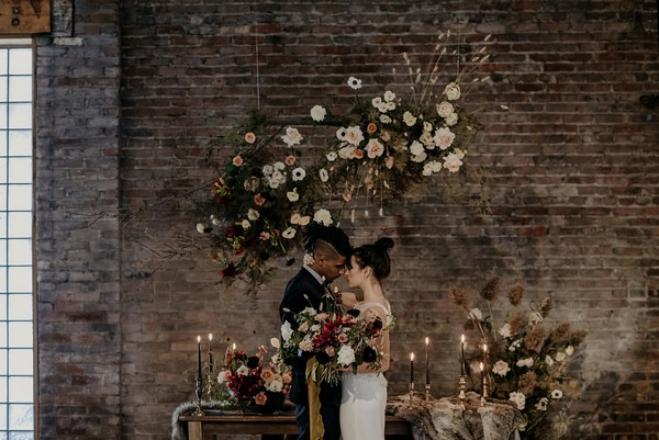 Bride and groom standing in front of table with autumn wedding styling and floral displays