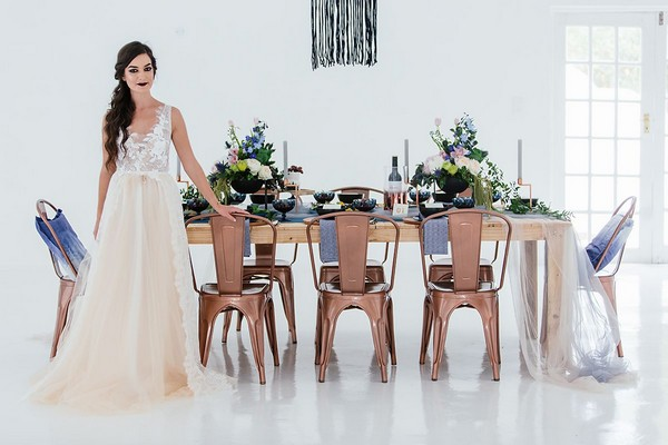 Bride standing in front of wedding table with blue and copper styling