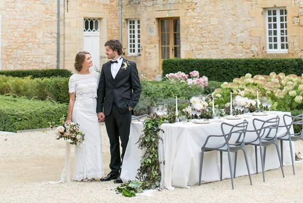 Bride and groom standing by table with organic wedding styling