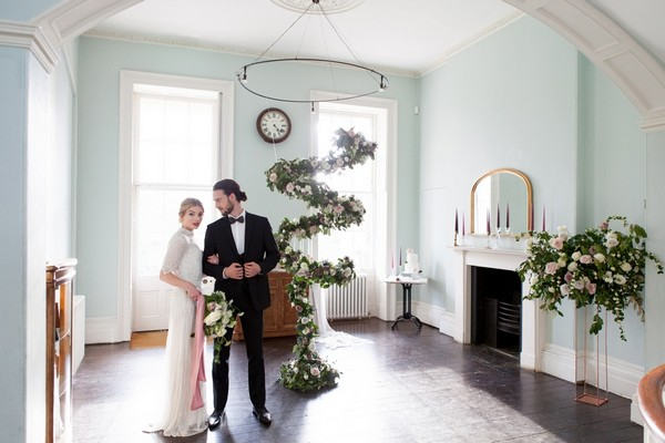 Bride and groom in Clissold House next to spiral floral feature