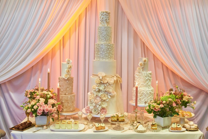 Three Wedding Cakes with Varying Tiers on Table