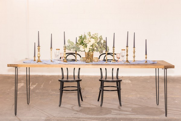 Wedding table in East Crossing with black chairs, gold candlesticks and floral centrepiece