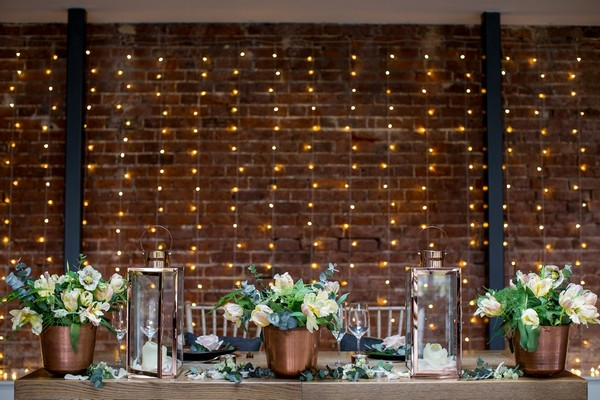 Foliage and copper wedding styling on wooden table