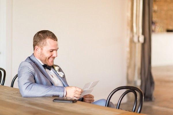 Groom smiling as he reads note from bride