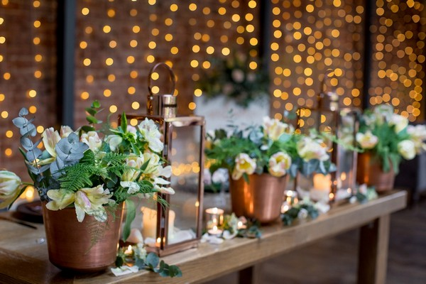 Copper pots of flowers and lanterns on wedding table