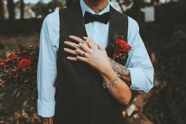 Groom holding bride's hand against his chest