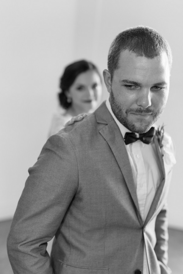 Groom about to turn and see bride