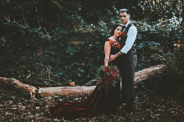 Bride resting head against groom's chest in woods