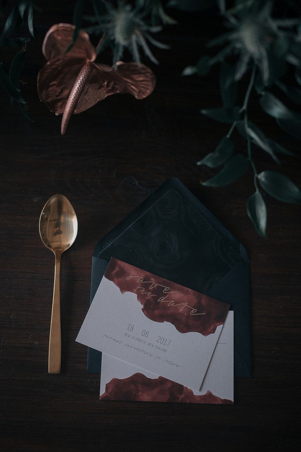 Dark stationery and gold cutlery for industrial wedding
