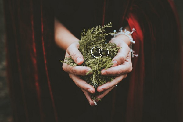 Bride holding handful of fern with wedding rings on top