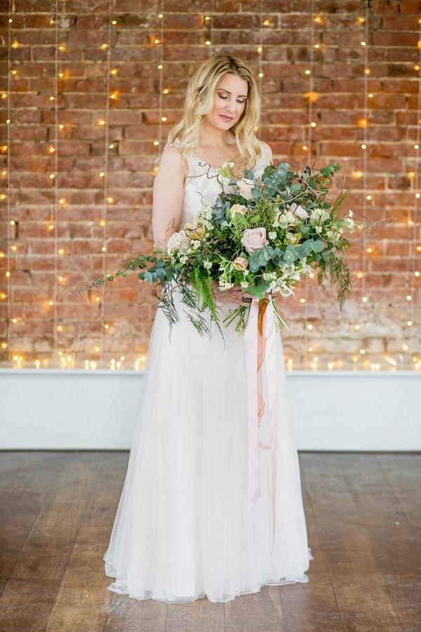 Bride holding wild oversized foliage bouquet