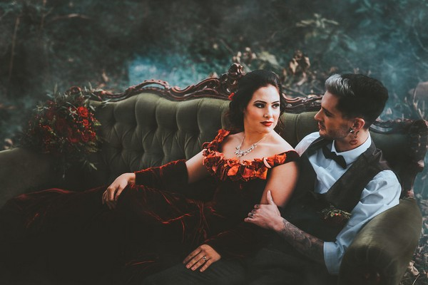 Bride and groom sitting on couch in woods