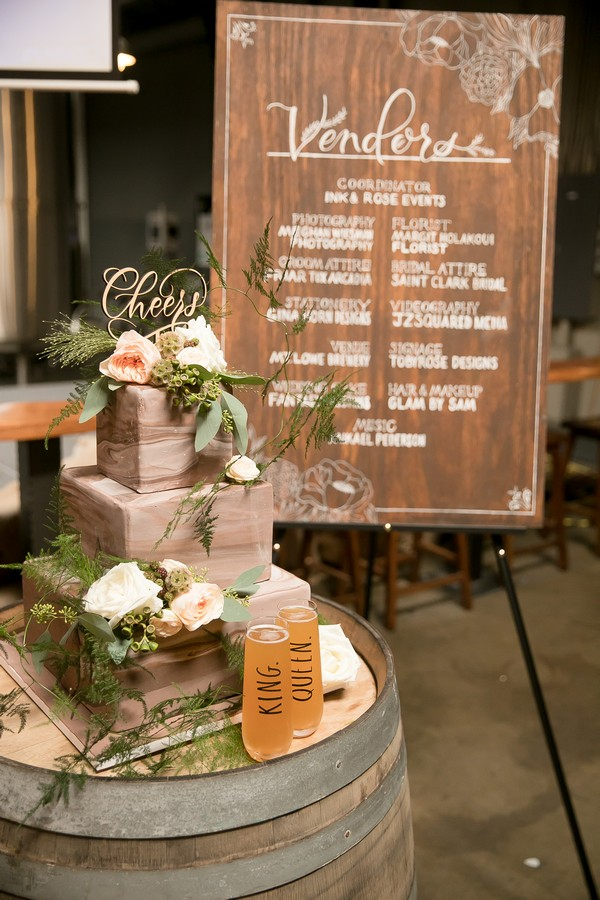 Wedding cake on barrel in front of vendor sign