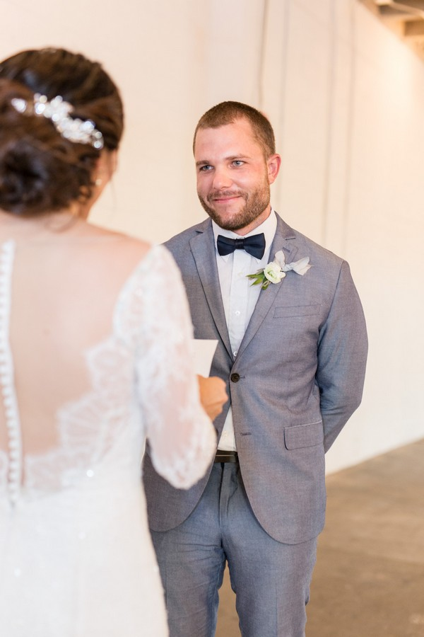 Groom smiling as bride reads wedding vows