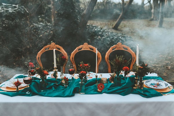 Wedding table in woods with teal runner and red flowers