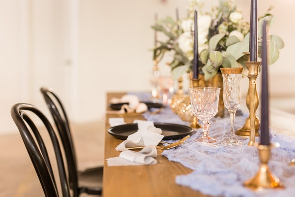 Elegant wedding table styling with black plates, tulle table runner and gold candlesticks