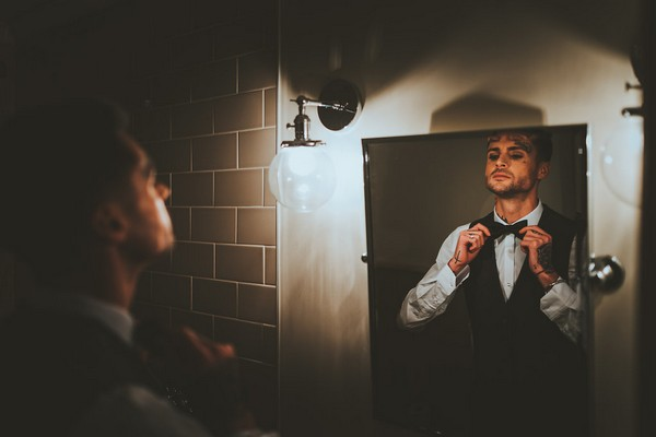 Groom doing up bow tie in mirror