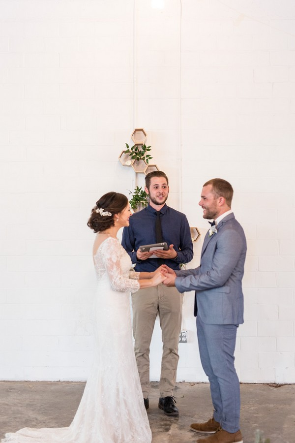 Bride and groom holding hands as celebrant conducts wedding ceremony at East Crossing
