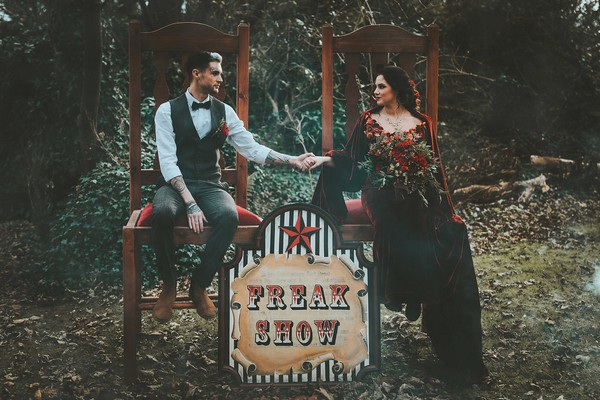 Bride and groom sitting on chairs next to 1920's carnival freak show sign