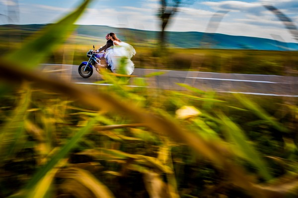Bride and groom riding down country road on motorbike - Picture by DA Studio