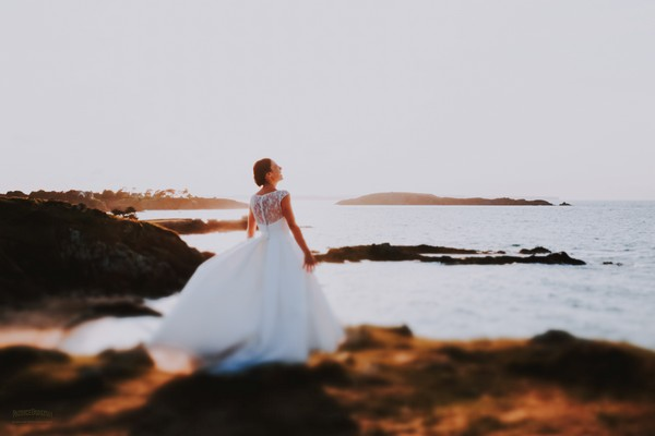Bride standing by sea looking up at the sky - Picture by Patrice Dorizon