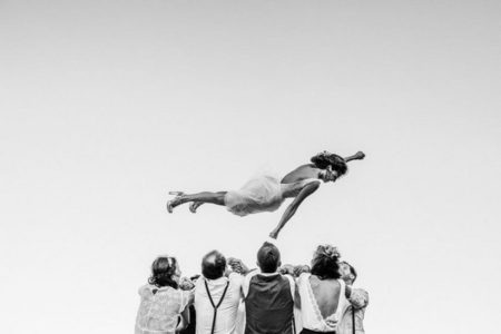 Bridal party throwing bride into the air - Picture by Alison Bounce Photography