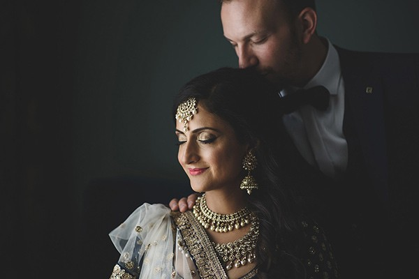 Groom kissing back of Indian bride's head - Picture by Rik Pennington Photography
