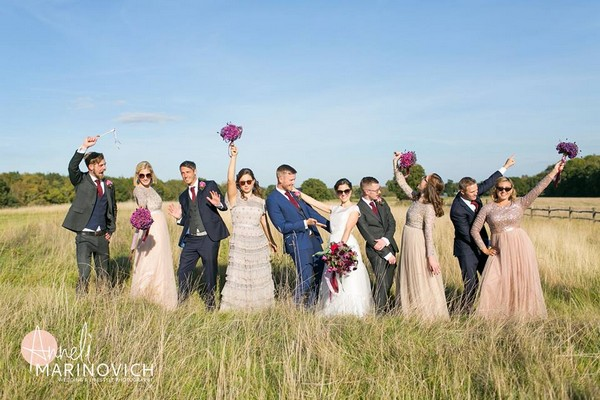 Bridal party posing in field for photograph - Picture by Anneli Marinovich Photography
