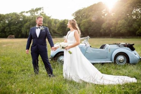 Bride and groom standing in field in front of convertible wedding car - Picture by Shan Fisher Photography