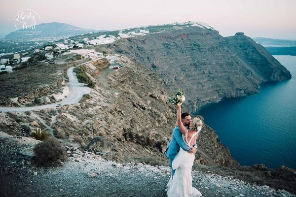 Bride and groom kissing on top of cliff overlooking the sea - Picture by Liberty Pearl Photography