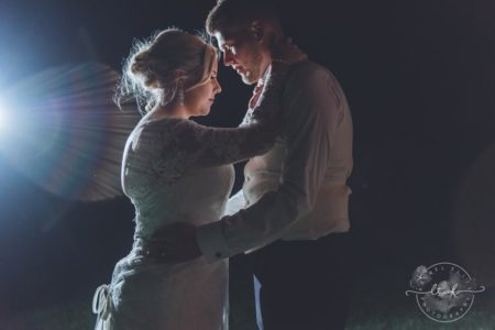 Bride and groom lit up by light at night - Picture by Life Through A Lens - Rachel Ellis Photography