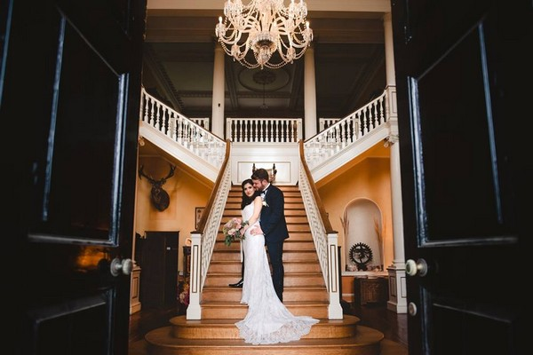 Bride and groom standing at bottom of staircase in entrance of wedding venue - Picture by Gina Manning Photography