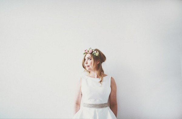 Bride standing up against white wall - Picture by On Love and Photography