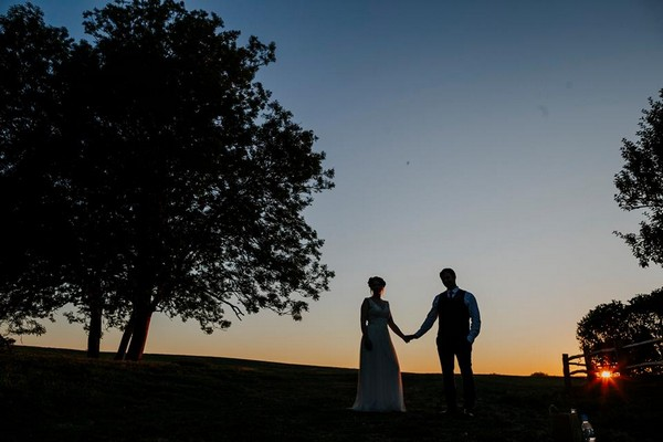 Bride and groom holding hands by tree at sunset - Picture by Joasis Photography