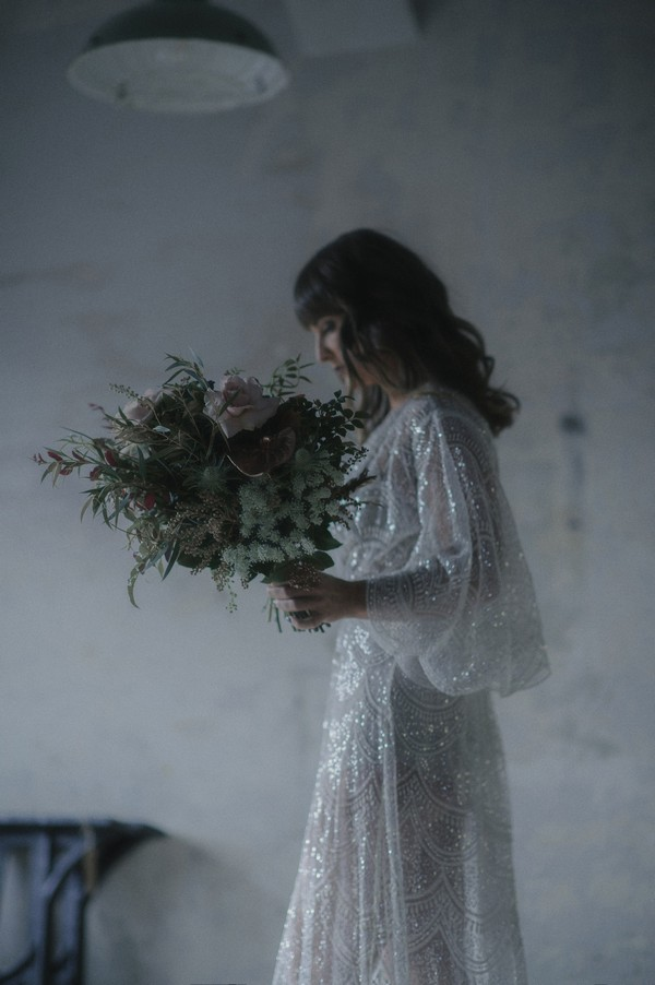 Bride carrying bouquet in warehouse