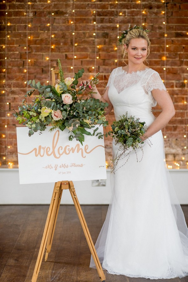Bride standing next to wedding welcome sign