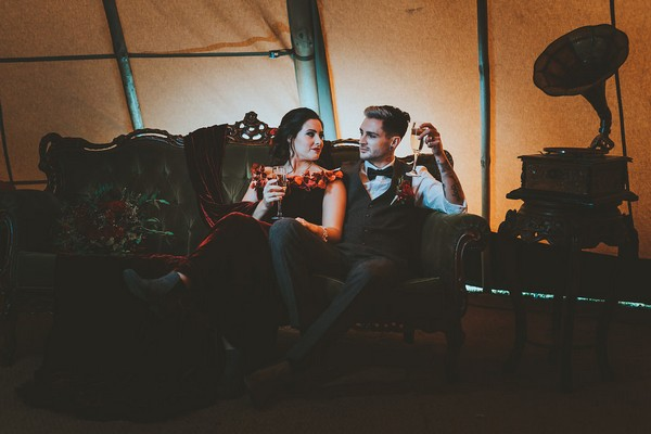 Bride and groom sitting on couch in tipi