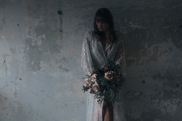 Bride holding bouquet standing against warehouse wall