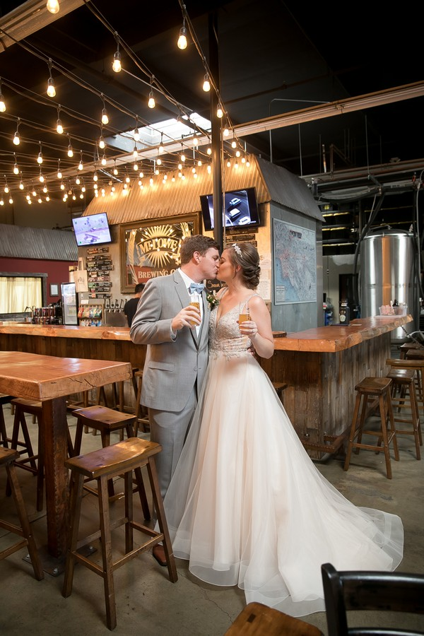 Bride and groom kissing by bar in Mt. Lowe Brewery
