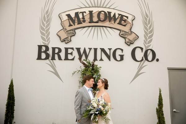 Bride and groom kissing in front of Mt. Lowe Brewing Co. sign