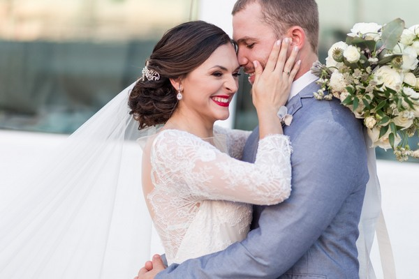 Bride with hands on groom's face