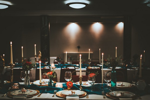 Wedding tables dressed with teal runners and candles