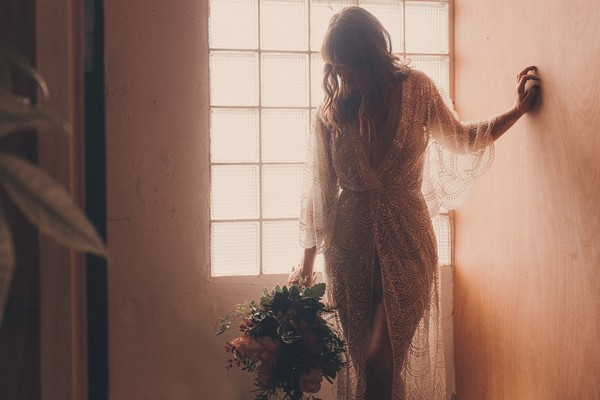 Bride holding bouquet in front of window