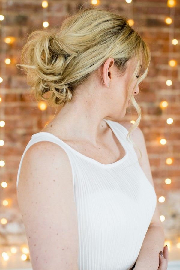 Bride showing back of messy updo hairstyle