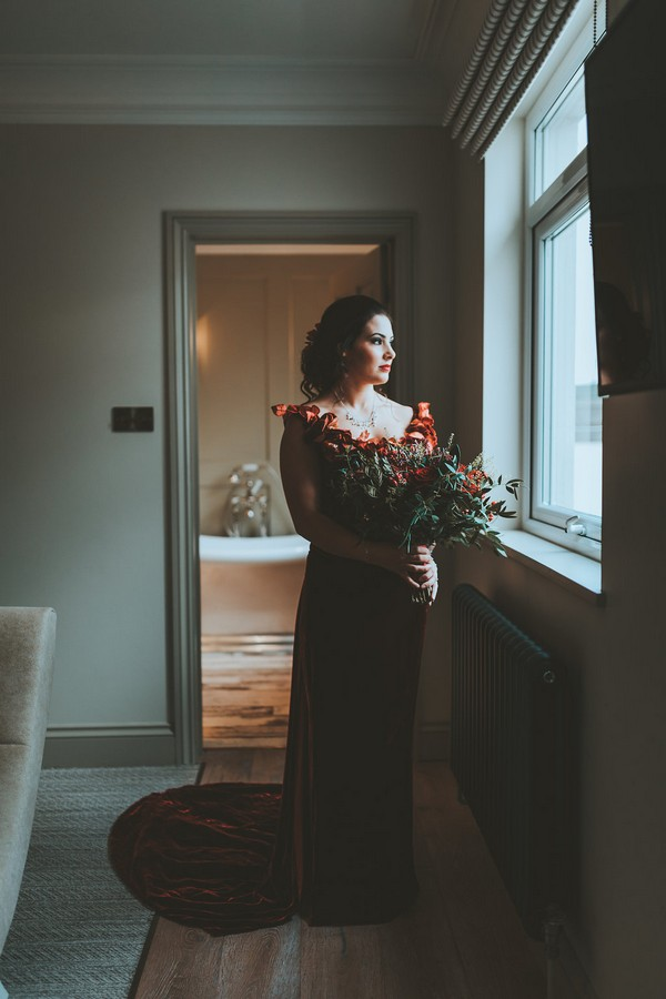 Bride holding bouquet looking out of window