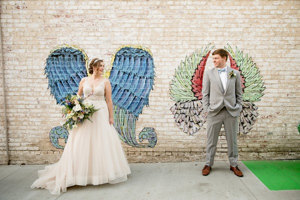 Bride and groom standing in front of wing graffiti artwork on wall