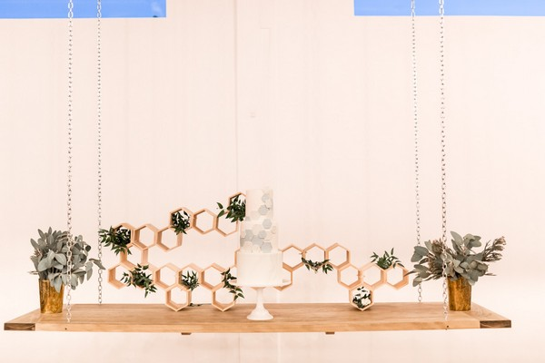 Wedding cake with hexagon detail suspended from ceiling
