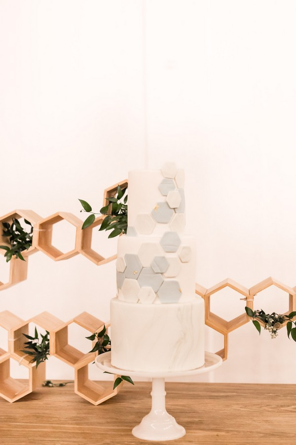 Wedding cake with hexagon detail in front of honeycomb shaped backdrop