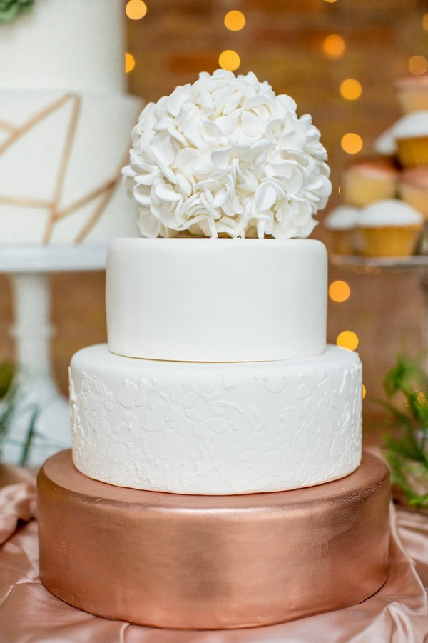 Copper and white wedding cake topped with sugar hydrangea head