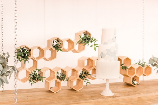 Wedding cake with hexagon detail in front of honeycomb style backdrop